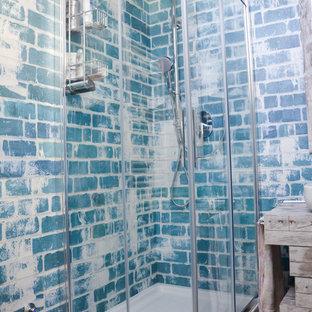 Modelo de cuarto de baño con ducha, industrial, de tamaño medio, con armarios con paneles lisos, puertas de armario de madera clara, ducha esquinera, sanitario de pared, baldosas y/o azulejos grises, paredes multicolor, suelo de madera en tonos medios, lavabo sobreencimera y encimera de laminado