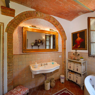 Inspiration for a mediterranean bathroom in Florence with a freestanding bath, terracotta tiles, white walls and a wall-mounted sink.