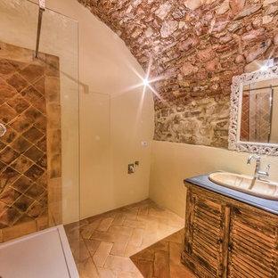 Immagine di una stanza da bagno padronale tradizionale di medie dimensioni con ante a persiana, ante in legno chiaro, doccia ad angolo, piastrelle in terracotta, pareti beige, pavimento in terracotta, lavabo integrato e top in pietra calcarea