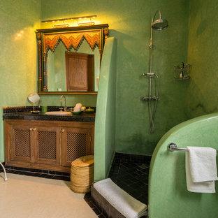 Immagine di una stanza da bagno con doccia mediterranea con pareti verdi, doccia aperta, ante con riquadro incassato, ante in legno scuro, doccia ad angolo, lavabo da incasso, pavimento beige e top nero