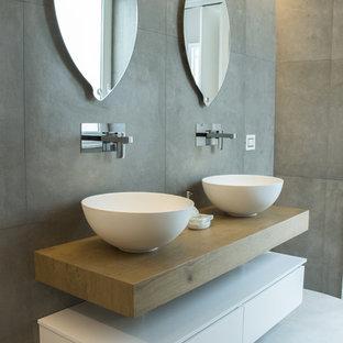 Ispirazione per una stanza da bagno padronale contemporanea con piastrelle grigie, piastrelle in gres porcellanato, lavabo a bacinella, ante lisce, ante bianche, pareti grigie, top in legno, pavimento bianco e top marrone