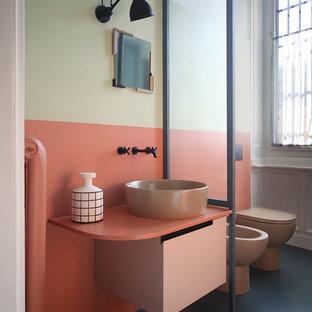 Bild på ett mellanstort eklektiskt badrum, med orange kakel, ett fristående handfat, svart golv, släta luckor, en toalettstol med hel cisternkåpa, flerfärgade väggar och betonggolv