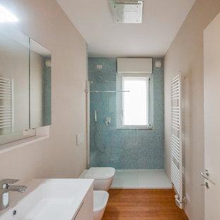 Ispirazione per una stanza da bagno con doccia minimal di medie dimensioni con ante lisce, ante bianche, doccia alcova, WC sospeso, piastrelle blu, piastrelle di vetro, pareti beige, pavimento in bambù, lavabo a consolle, top in superficie solida, porta doccia a battente e top bianco