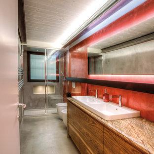 Esempio di una stanza da bagno con doccia design di medie dimensioni con ante lisce, WC sospeso, pareti rosse, lavabo da incasso, porta doccia scorrevole, pavimento in cemento, pavimento grigio, ante in legno scuro, doccia alcova e top marrone
