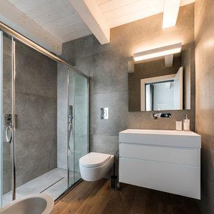 Idéer för att renovera ett mellanstort funkis en-suite badrum, med släta luckor, vita skåp, en dusch i en alkov, en bidé, grå väggar, mellanmörkt trägolv, ett väggmonterat handfat, brunt golv, dusch med skjutdörr och grå kakel