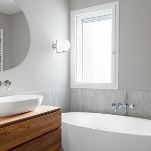 Esempio di una stanza da bagno con doccia design con ante lisce, ante in legno bruno, vasca freestanding, piastrelle grigie, pareti grigie, lavabo a bacinella, top in legno e top marrone