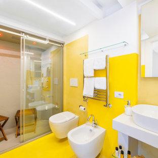 Foto de cuarto de baño con ducha, moderno, de tamaño medio, con puertas de armario blancas, ducha a ras de suelo, sanitario de pared, paredes amarillas, suelo de cemento, encimera de cemento, suelo amarillo, ducha abierta y encimeras blancas