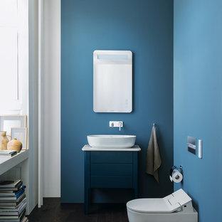 Foto di una piccola stanza da bagno minimal con ante blu, lavabo a bacinella, top in quarzo composito, ante lisce, WC sospeso, pareti blu, parquet scuro, pavimento marrone e top bianco