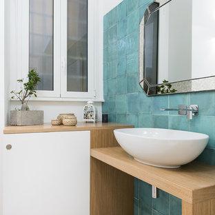 Esempio di una stanza da bagno con doccia minimal di medie dimensioni con ante lisce, ante in legno chiaro, bidè, pareti blu, lavabo a bacinella, top in legno, pavimento grigio, piastrelle blu e top beige