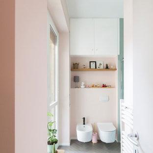 На фото: маленькая ванная комната в стиле модернизм с плоскими фасадами, зелеными фасадами, угловым душем, инсталляцией, зеленой плиткой, керамической плиткой, розовыми стенами, полом из керамогранита, душевой кабиной, настольной раковиной, столешницей из ламината, серым полом, душем с раздвижными дверями, белой столешницей, нишей, тумбой под одну раковину, напольной тумбой и панелями на части стены