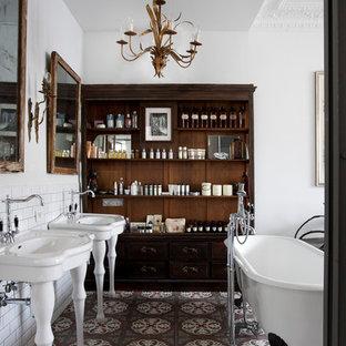 Inspiration pour une salle de bain principale bohème de taille moyenne avec un plan vasque, un placard sans porte, des portes de placard en bois sombre, une baignoire sur pieds, un mur blanc et une douche d'angle.