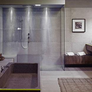 Diseño de cuarto de baño industrial con lavabo integrado, armarios abiertos, encimera de cemento, bañera exenta, ducha abierta, baldosas y/o azulejos grises, baldosas y/o azulejos de cemento, paredes grises, suelo de cemento y ducha abierta
