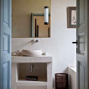 Immagine di una stanza da bagno mediterranea con pareti beige, lavabo a bacinella, pavimento beige e top beige