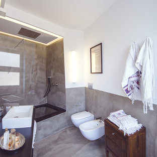 Modelo de cuarto de baño con ducha, mediterráneo, grande, con bañera empotrada, combinación de ducha y bañera, sanitario de pared, paredes blancas, suelo de cemento y lavabo de seno grande