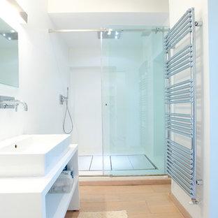 На фото: ванная комната среднего размера в стиле модернизм с белыми стенами, светлым паркетным полом, душевой кабиной, белыми фасадами, душем в нише, настольной раковиной, столешницей из ламината, душем с раздвижными дверями и открытыми фасадами с