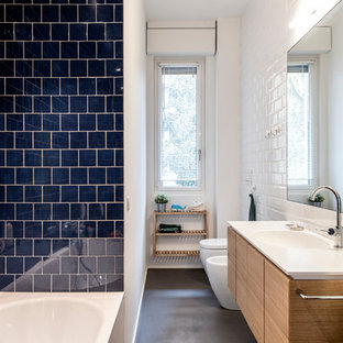 Photo of a medium sized scandinavian family bathroom in Milan with flat-panel cabinets, light wood cabinets, an alcove bath, a two-piece toilet, blue tiles, ceramic tiles, white walls, concrete flooring, an integrated sink, solid surface worktops, grey floors and white worktops.
