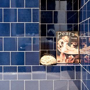 Modelo de cuarto de baño principal, nórdico, de tamaño medio, con armarios con paneles lisos, puertas de armario de madera clara, ducha empotrada, sanitario de dos piezas, baldosas y/o azulejos blancas y negros, baldosas y/o azulejos de terracota, paredes blancas, suelo de cemento, lavabo integrado, encimera de acrílico, suelo gris, ducha con puerta con bisagras y encimeras blancas