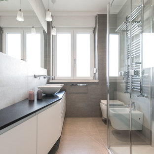 Mid-sized contemporary bathroom in Cagliari with grey walls, porcelain floors, flat-panel cabinets, white cabinets, a bidet, a vessel sink, a hinged shower door, black benchtops, beige tile, gray tile and beige floor.