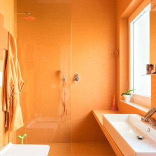 Imagen de cuarto de baño con ducha, bohemio, con puertas de armario naranjas, ducha abierta, sanitario de dos piezas, baldosas y/o azulejos naranja, baldosas y/o azulejos en mosaico, parades naranjas, suelo de madera clara, lavabo sobreencimera, encimera de azulejos, ducha abierta y encimeras naranjas