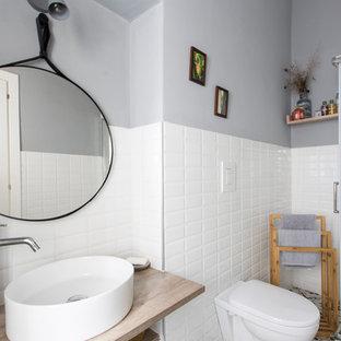 Неиссякаемый источник вдохновения для домашнего уюта: ванная комната среднего размера в скандинавском стиле с открытыми фасадами, коричневыми фасадами, угловым душем, раздельным унитазом, белой плиткой, керамической плиткой, разноцветными стенами, полом из мозаичной плитки, душевой кабиной, настольной раковиной, столешницей из дерева, разноцветным полом, душем с раздвижными дверями и коричневой столешницей