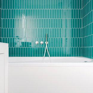 Ejemplo de cuarto de baño infantil, actual, pequeño, con armarios con paneles lisos, puertas de armario blancas, bañera empotrada, baldosas y/o azulejos azules, baldosas y/o azulejos verdes, baldosas y/o azulejos de porcelana, paredes blancas, suelo de baldosas de porcelana, encimera de acrílico, suelo blanco, encimeras blancas, combinación de ducha y bañera y ducha abierta