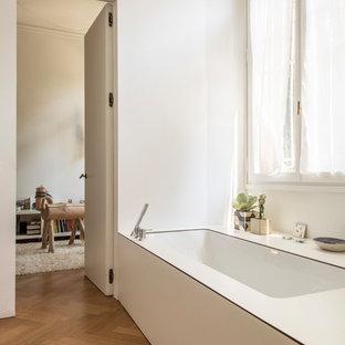 Ispirazione per una piccola stanza da bagno padronale scandinava con pavimento in legno massello medio, top in laminato, top bianco, vasca sottopiano, pareti bianche e pavimento marrone