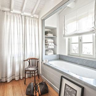 Immagine di una stanza da bagno padronale mediterranea con vasca sottopiano, pareti bianche e pavimento in legno massello medio