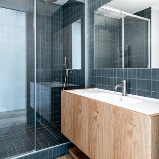 Esempio di una stanza da bagno moderna con ante a filo, ante in legno scuro, pavimento in legno massello medio e top bianco