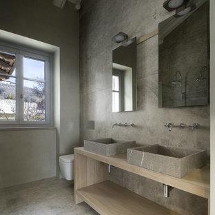 Foto di una stanza da bagno moderna con nessun'anta, ante in legno chiaro, WC sospeso, pareti grigie, pavimento in cemento, lavabo a bacinella e pavimento grigio
