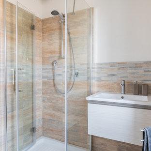 Immagine di una piccola stanza da bagno con doccia minimal con ante lisce, ante in legno chiaro, doccia ad angolo, WC a due pezzi, piastrelle multicolore, piastrelle in gres porcellanato, pareti bianche, pavimento in gres porcellanato, lavabo integrato, pavimento beige e porta doccia scorrevole