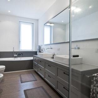 Esempio di una stanza da bagno contemporanea con ante grigie, vasca da incasso, WC sospeso, pareti bianche, parquet scuro, lavabo rettangolare e ante con riquadro incassato