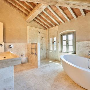 Esempio di una stanza da bagno padronale mediterranea con vasca freestanding, doccia a filo pavimento, WC sospeso, piastrelle beige, pareti beige, lavabo rettangolare, pavimento beige e doccia aperta