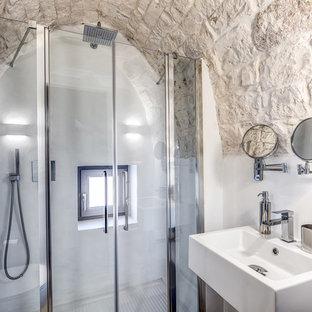 Immagine di una stanza da bagno mediterranea con doccia alcova, pareti bianche, lavabo sospeso e porta doccia a battente