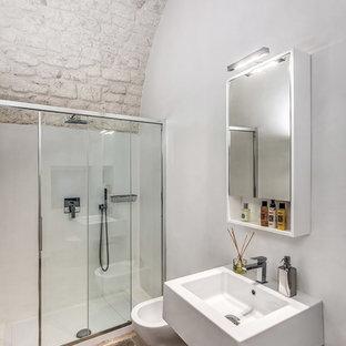 Immagine di una stanza da bagno mediterranea con doccia alcova, WC sospeso, pareti bianche, lavabo sospeso, pavimento marrone e porta doccia scorrevole