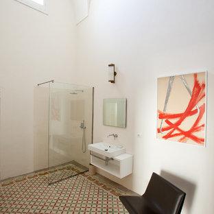 Foto på ett mellanstort medelhavsstil badrum med dusch, med öppna hyllor, vita skåp, en kantlös dusch, en vägghängd toalettstol, vita väggar, ett väggmonterat handfat och med dusch som är öppen