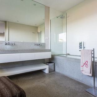 Idee per una stanza da bagno padronale design di medie dimensioni con ante lisce, ante bianche, vasca ad angolo, vasca/doccia, pareti bianche, pavimento in cemento, lavabo sottopiano, top in cemento e doccia aperta