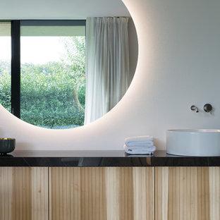 Esempio di una stanza da bagno minimalista con ante lisce, ante in legno chiaro, pareti bianche, lavabo a bacinella, pavimento grigio e top nero