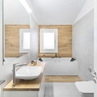 Idee per una piccola stanza da bagno padronale design con ante lisce, ante bianche, vasca ad alcova, vasca/doccia, WC sospeso, piastrelle grigie, piastrelle in ceramica, lavabo a bacinella, top in legno, doccia aperta, pareti grigie, pavimento grigio e top beige