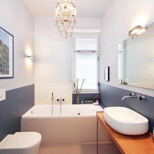 Esempio di una piccola stanza da bagno con doccia minimal con ante lisce, vasca da incasso, WC sospeso, pareti grigie, lavabo a bacinella, top in legno, pavimento beige e top marrone