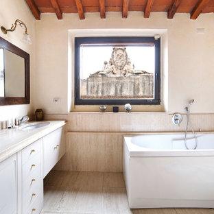Esempio di una stanza da bagno mediterranea con ante lisce, ante bianche, vasca freestanding, vasca/doccia, piastrelle beige, pareti bianche, lavabo sottopiano, pavimento beige, doccia aperta e top beige