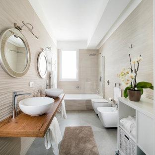 Esempio di una stanza da bagno con doccia con vasca ad alcova, vasca/doccia, bidè, piastrelle beige, pareti beige, lavabo a bacinella, top in legno, pavimento grigio, porta doccia a battente e top marrone