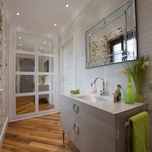 Foto di una stanza da bagno con doccia design di medie dimensioni con ante lisce, ante grigie, piastrelle grigie, pareti beige, pavimento in legno massello medio, lavabo integrato, pavimento marrone e top grigio
