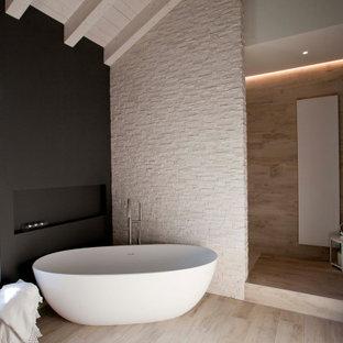 Immagine di una grande stanza da bagno padronale design con vasca freestanding, piastrelle beige, pareti nere e pavimento beige