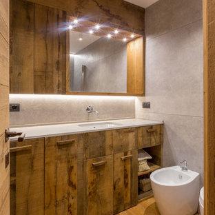 Ejemplo de cuarto de baño con ducha, rústico, con puertas de armario de madera oscura, suelo de madera en tonos medios, armarios con paneles lisos, bidé, baldosas y/o azulejos grises, lavabo bajoencimera, suelo marrón y encimeras blancas