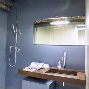 Ispirazione per una stanza da bagno con doccia industriale di medie dimensioni con ante di vetro, ante blu, doccia aperta, WC sospeso, pareti blu, pavimento in cemento, lavabo sottopiano, top in legno, pavimento bianco e porta doccia scorrevole