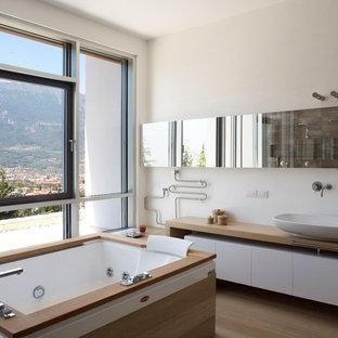 Ispirazione per una grande stanza da bagno padronale con vasca idromassaggio, lavabo a bacinella, top in legno, pareti bianche, parquet chiaro e pavimento beige
