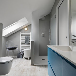 Foto de cuarto de baño principal, moderno, pequeño, con puertas de armario azules, ducha esquinera, sanitario de pared, baldosas y/o azulejos grises, paredes grises, suelo de baldosas de porcelana y lavabo integrado