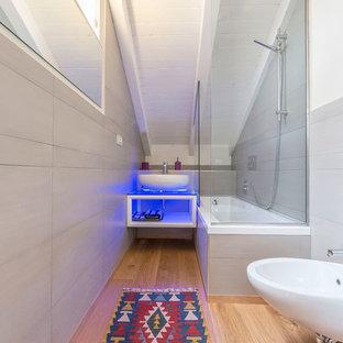 Stilmix Badezimmer mit Wandtoilette, beiger Wandfarbe, braunem Holzboden, beigem Boden, offenen Schränken, weißen Schränken, Eckbadewanne, Duschbadewanne, grauen Fliesen, Aufsatzwaschbecken und offener Dusche in Sonstige
