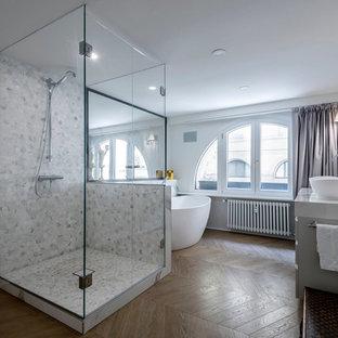 Idee per una grande stanza da bagno padronale minimal con vasca freestanding, pareti bianche, pavimento in legno massello medio, lavabo a bacinella, pavimento marrone, porta doccia a battente, ante grigie, piastrelle multicolore e top in marmo