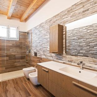 Immagine di una piccola stanza da bagno con doccia moderna con ante in legno scuro, doccia aperta, bidè, piastrelle multicolore, piastrelle di pietra calcarea, lavabo da incasso, top in superficie solida, doccia aperta e top bianco